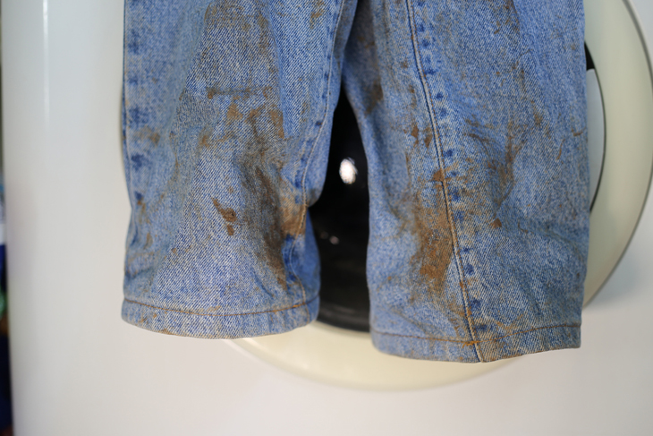Muddy jeans on a washing machine. Mud stain on jeans. Stained jeans before laundry.